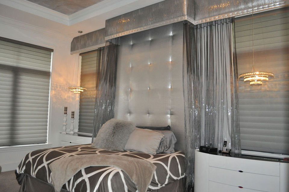 In this Grey Oaks home we designed and installed this custom silver and diamond studded headboard. The canopy over the bed was created using silk and sequinned sheers overlay with a diamond nailhead border.