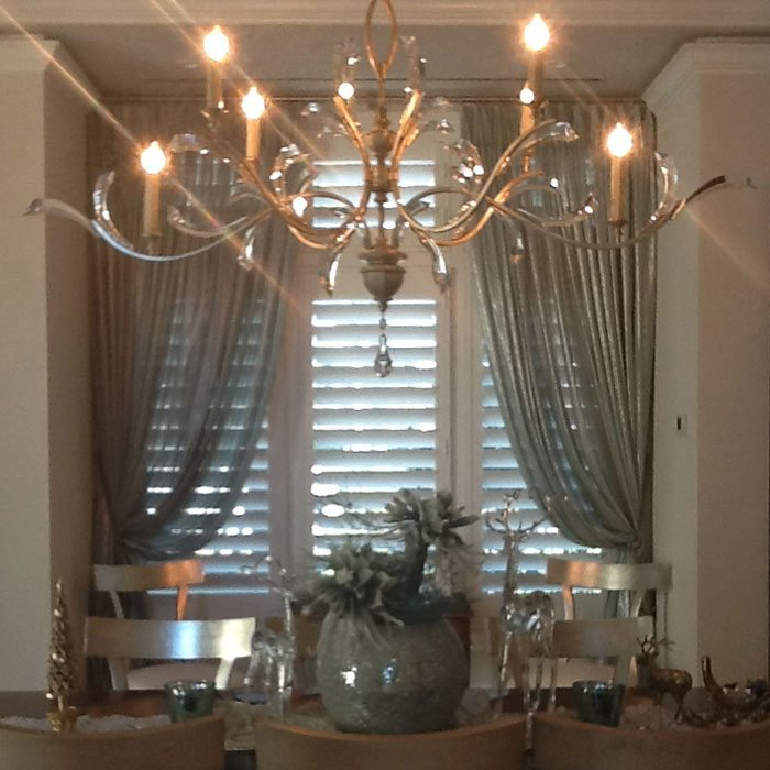Aqua coloured metallic sheers frame the window in this Elegant Tiburon Estates home Dining Room. The very full French pleated sheers hang from a brushed nickel rod which complements the lighting fixture.