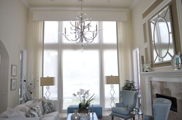 Sheer weave roller shades diffuse the afternoon sunshine in this Quail West home. When not in use they hide underneath the upholstered cornice. Decorative banding was used to pull together the drapes and the upholstery in the room.