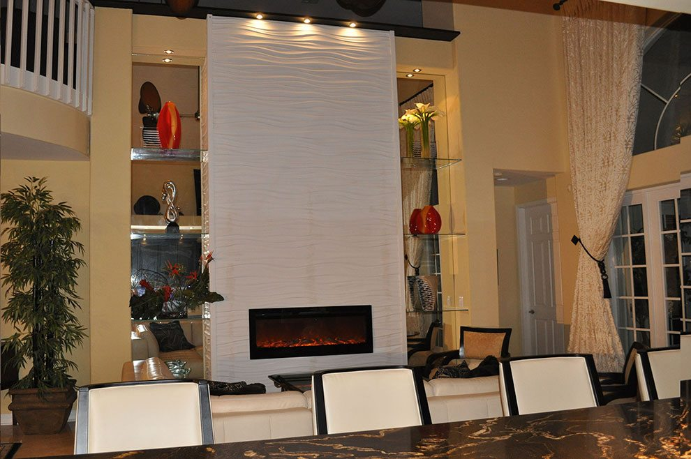 This blank wall was given the wow factor by designing a 1.5 storey fireplace with mirror display shelves on either side. The Module Art tiles create a soft wave design.
