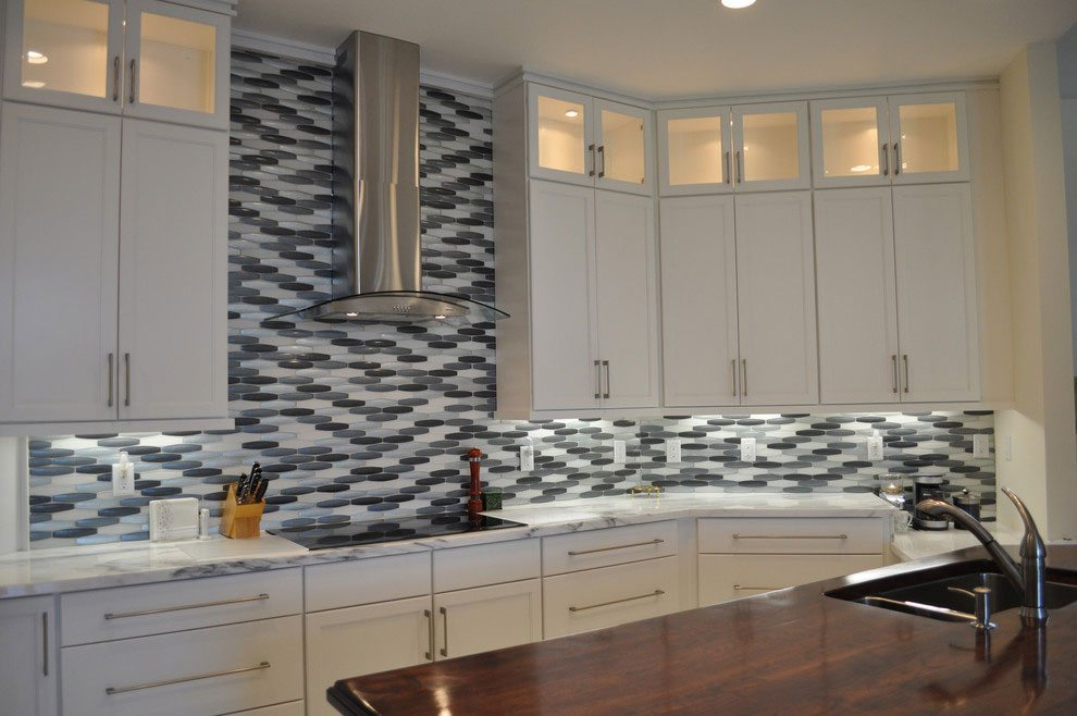 To create a more ergonomic and functional work area, this Pelican Bay kitchen was totally reconfigured. Finishes include a bespoke Cherry Island, Carrera marble counters that are illuminated by LED under counter lights and Iridescent 4 colour glass tile on the backsplash.