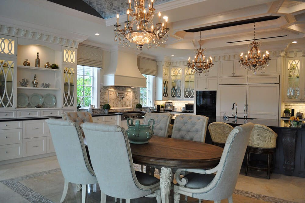 This elegant kitchen/ great room's windows are treated at the top with mock Roman valances in a platinum and silver geometric design with a beaded trim that reflects the light fixtures.