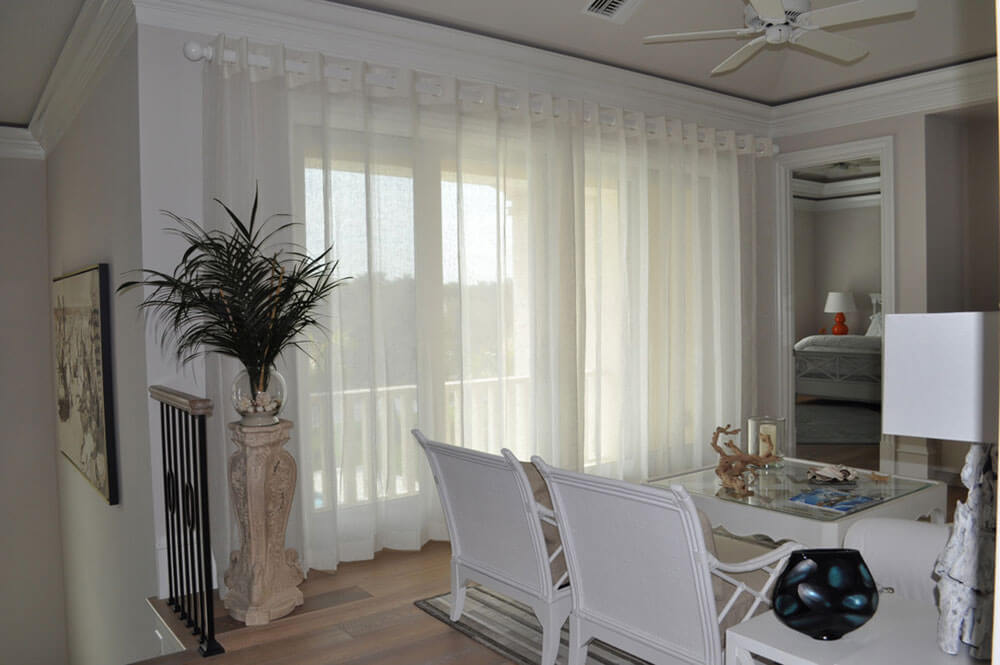 White linen grommet style draw drapes, softly diffuse the western sunshine in this loft area.