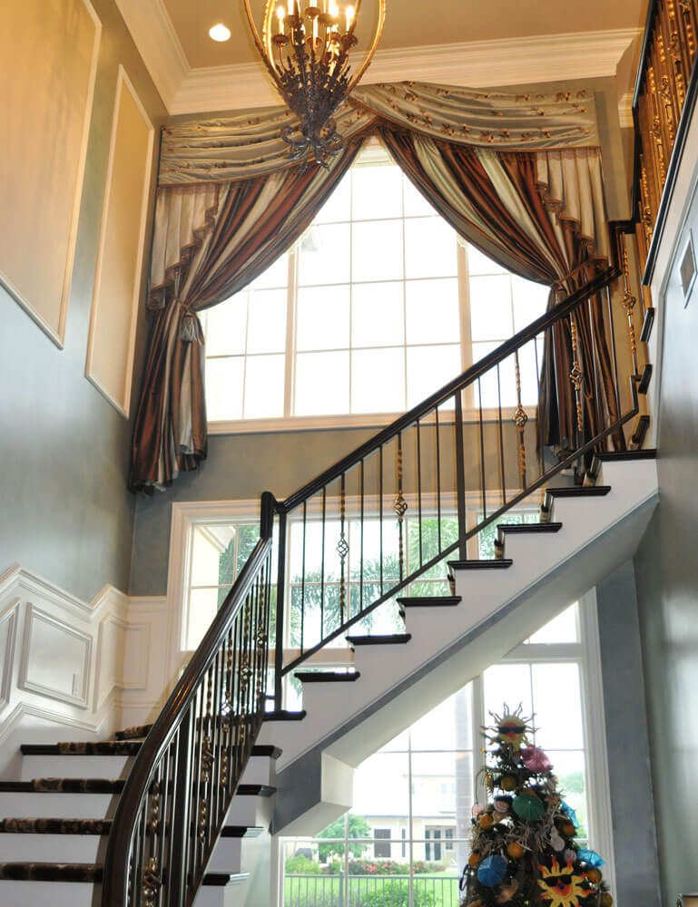 In this 2 story entrance hall we installed this gorgeous custom striped huge valance. Cirque du Soleil would have be proud of the way we installed it.