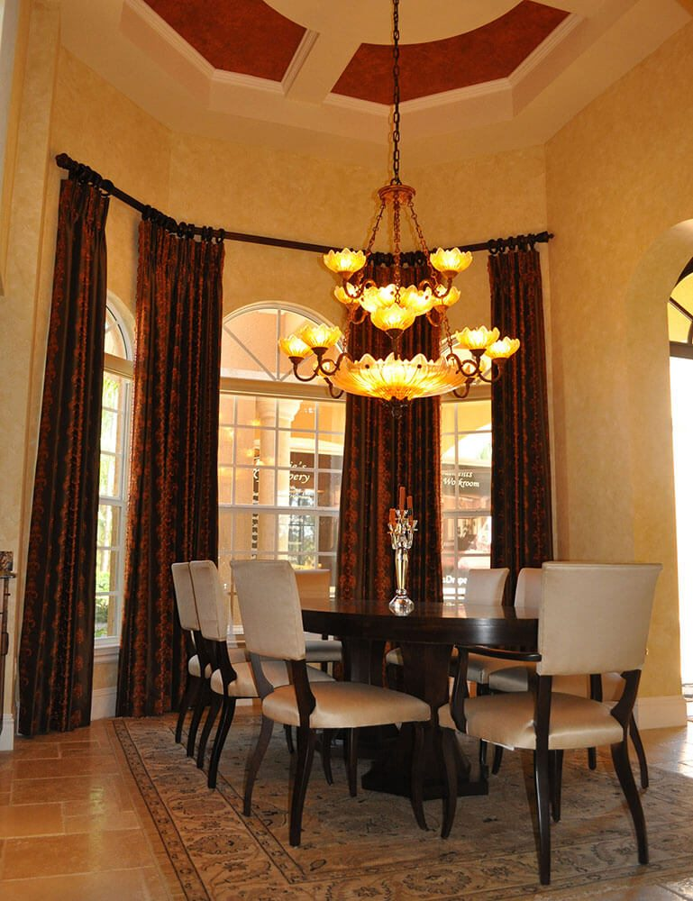 Pirouette blinds stack discreetly below the arched windows of this dining room and give privacy when needed. The elegant faux silk embroidered side panels hang from Walnut finished rods soften and frames each window. The height of the side panels was taken above the transom arches , allowing your eye to continue to the faux ceiling detail.