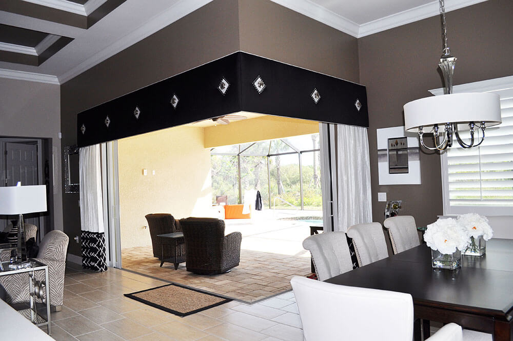 "This window treatment Designed by Frankie Rojas has a Black and Silver theme in this contemporary Great Room. The padded cornices are upholstered in Black silk with round chrome finished medallions on silver squares trimmed with diamond nail heads. The side panels are a metallic silver linen with a 24"" contrast fabric at the bottom in a black & sliver geometric, this balances the weight of the dark cornice at the top"