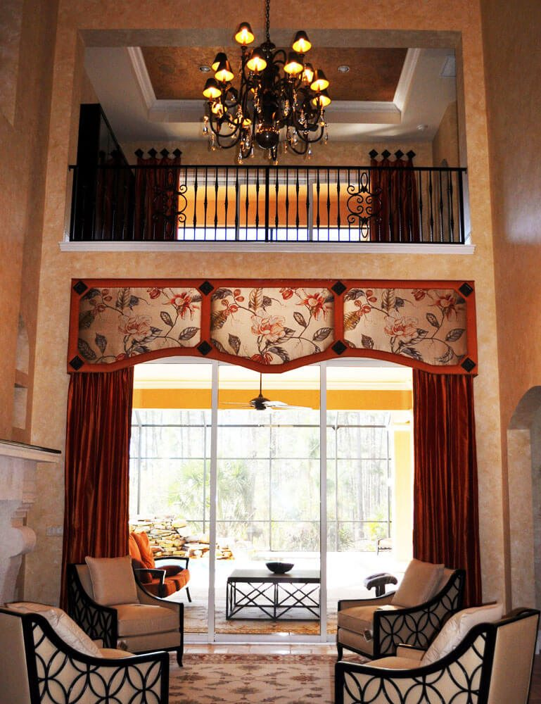As you walk from the Porte Cochere into this two storey Formal Living Room you are greeted by a stunning silk Crushed orange and soft beige floral padded cornice. The floral has a huge pattern repeat, as the room is so large. Silk crushed orange side panels flank the lower window. As your eyes move up to the second level , you see the same fabrics but treated in a different manor with medallions.