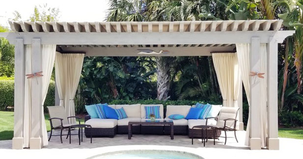 Soft beige outdoor sheer fabric has been used here in this Pelican Bay home. The front of the Cabanna has a west exposure so the sheers draw together for added sun protection. The rest of the sheers are stationary and held back with Bronze metal hardware.