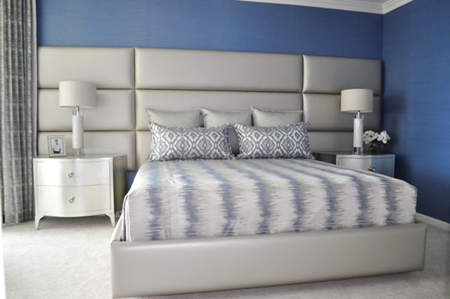 We created this luxurious bedroom in a waterfront condo in Seagate , Naples by upholstering the headboard wall with 9  metallic faux leather thick rectangular sculpted panels, with a matching platform bed. The walls are papered with a beautiful blue grass cloth, which pulls the blue from the bedding fabric.  The silver leaf night stands reflect the wall color and the bedding.